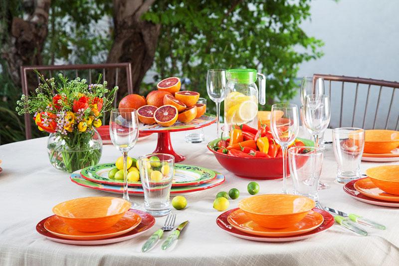 Летний вариант оформления – яркие оранжевые тарелки, вазы с летними фруктами и цветы