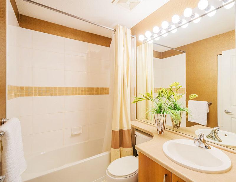 Отличный способ освещения совмещённой ванной комнаты – несколько обычных круглых лампочек, которые размещены над зеркалом и туалетом