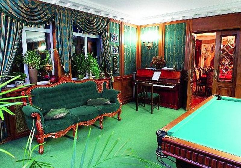 Бильярдный салон дополняет изящный диван на ножках и пианино в углу