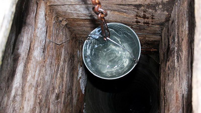 Чтобы получить воду из колодца, вам нужно сначала покрутить рычаг самодельного насоса с винтом, а потом набрать очищенную воду в ведро