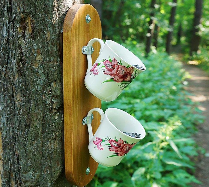 Можно сделать и вот такую кормушку, зафиксированную на стволе дерева. Просто используйте для крепления на доску ручки чашек. Сделать это можно полосками жести или даже просто кусочками кожи от ремня