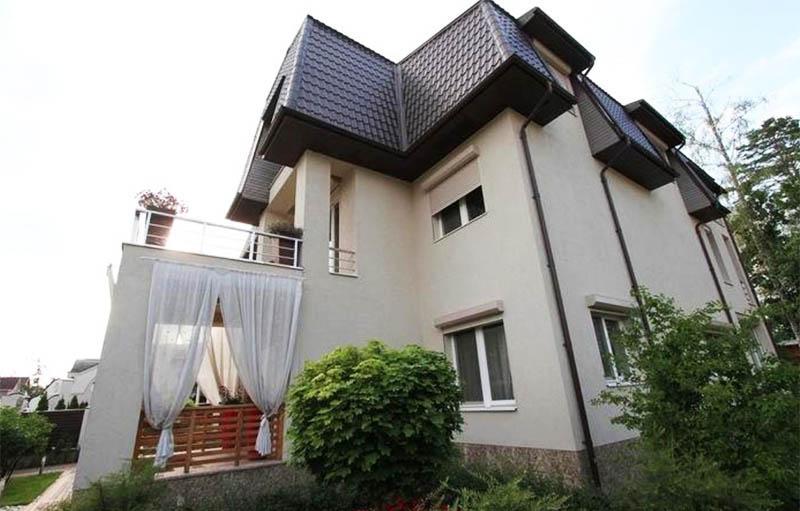 Светло-бежевый фасад дома удачно дополняет тёмно-коричневая кровля