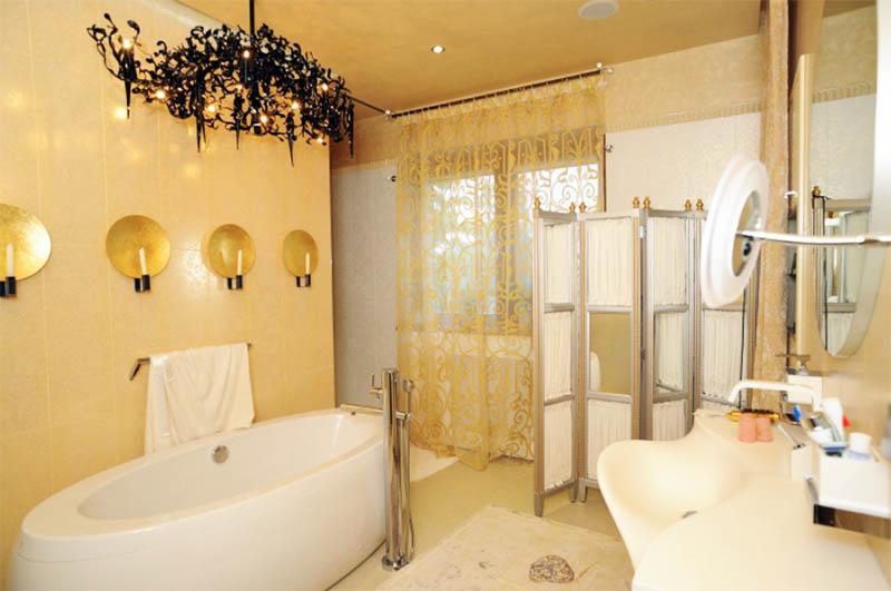 Дополняет оформление ванной комнаты красивый жёлтый тюль с густыми растительными узорами