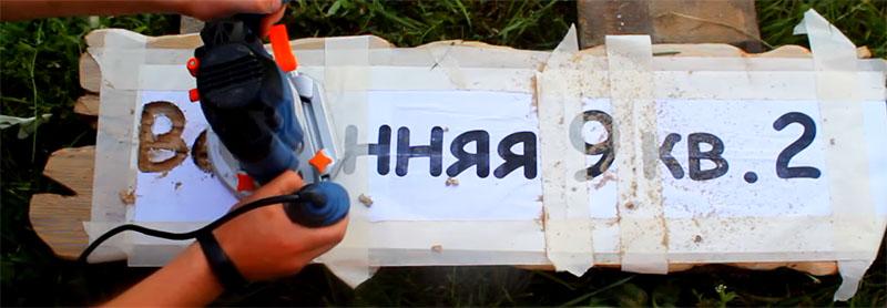Буквы в древесине выбираются фрезером вместе с бумагой