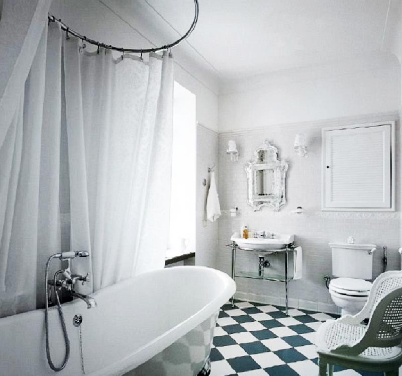 Над чашей ванны на хромированном карнизе закреплена белоснежная шторка