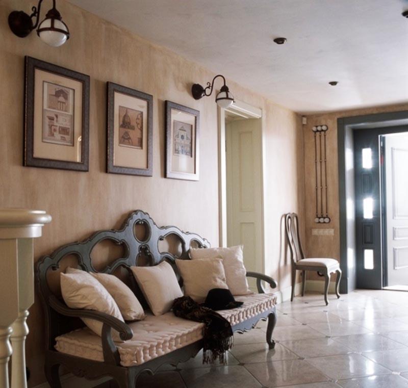 В просторном холле поставили элегантный диван с резной спинкой