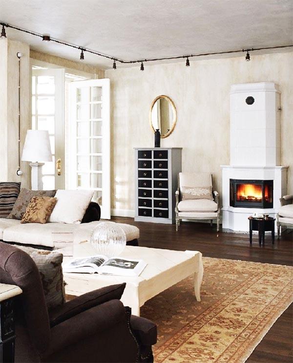 В качестве стильного украшения гостиной выбрали открытую электропроводку и шинные потолочные светильники чёрного цвета