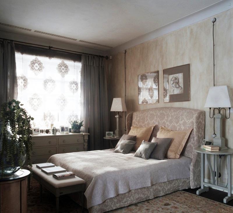 В спальне гармонично сочетаются геометрические принты на обоях, обивке спинки, ковре и тюле