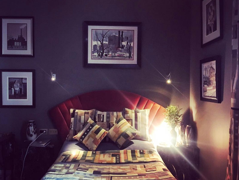 Над кроватью повесили небольшие ночники, в дополнение к ним на прикроватных тумбочках разместили дизайнерские настольные лампы