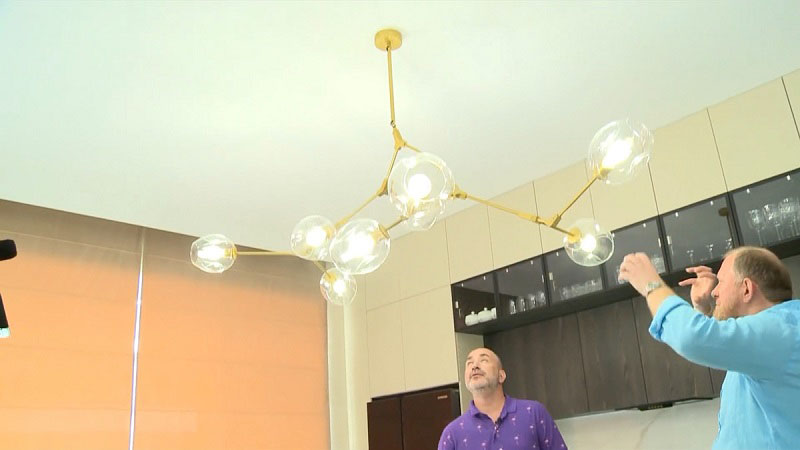 На потолке установили оригинальную люстру в виде молекул со стеклянными шарообразными плафонами, закреплёнными на жёлтом каркасе