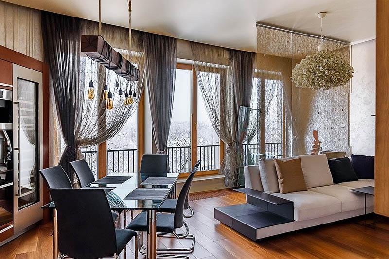 Диван украшен декоративными подушками, повторяющими основные цвета интерьера гостиной