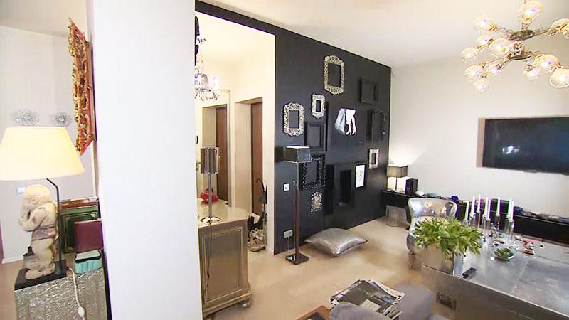 Чёрную стену в гостиной украшают старинные зеркальные рамы и современный камин с живым огнём