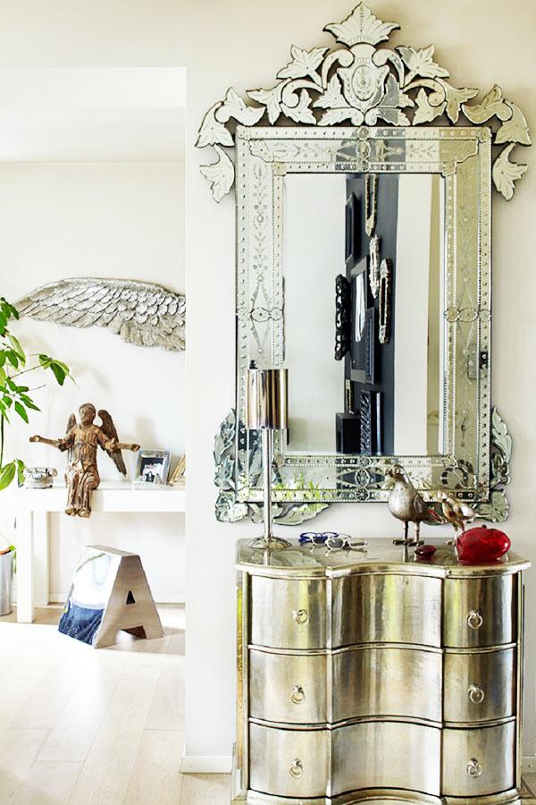 В прихожей над необычным серебристым комодом повесили уникальное венецианское зеркало