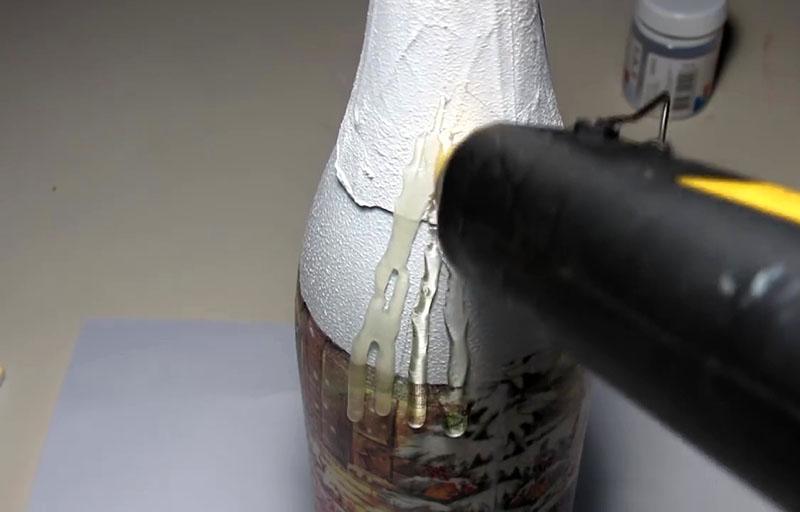 При помощи клеевого пистолета и термоклея делаем на горлышке бутылки имитацию восковых подтёков от свечи. Они обязательно должны зайти за границу салфетки по кругу