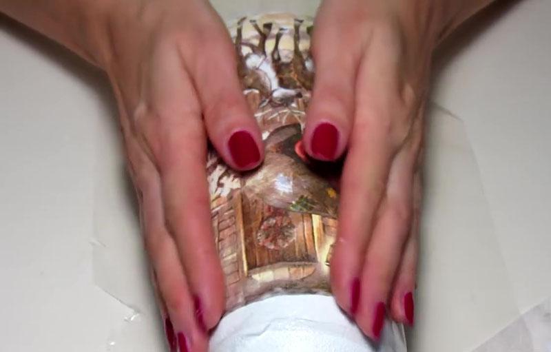 На наклеенную салфетку накладываем плотную плёнку и разглаживаем сквозь неё имеющиеся складки. Плёнка необходима, чтобы при разглаживании не порвать декоративный слой