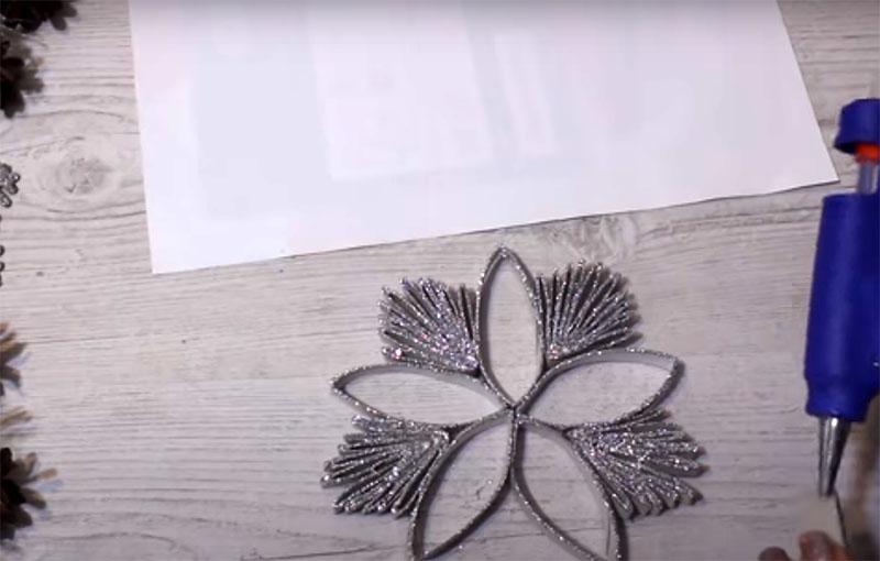 Между лепестками нужно вклеить листочки из нескольких колец. В центре снежинки рекомендуется приклеить бусину или другой декоративный элемент и зафиксировать ленту для крепления на вершине одного из колец
