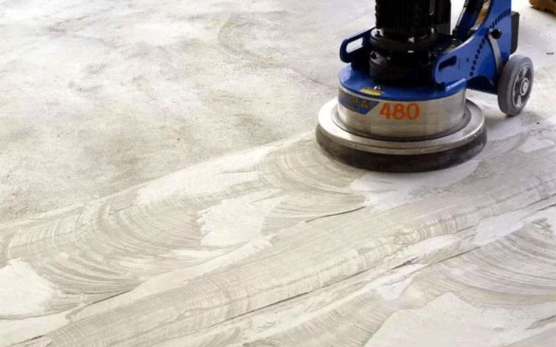 После бетонный пол шлифуют, чтобы увеличить его адгезивные свойства и удалить цементное молочко с поверхности