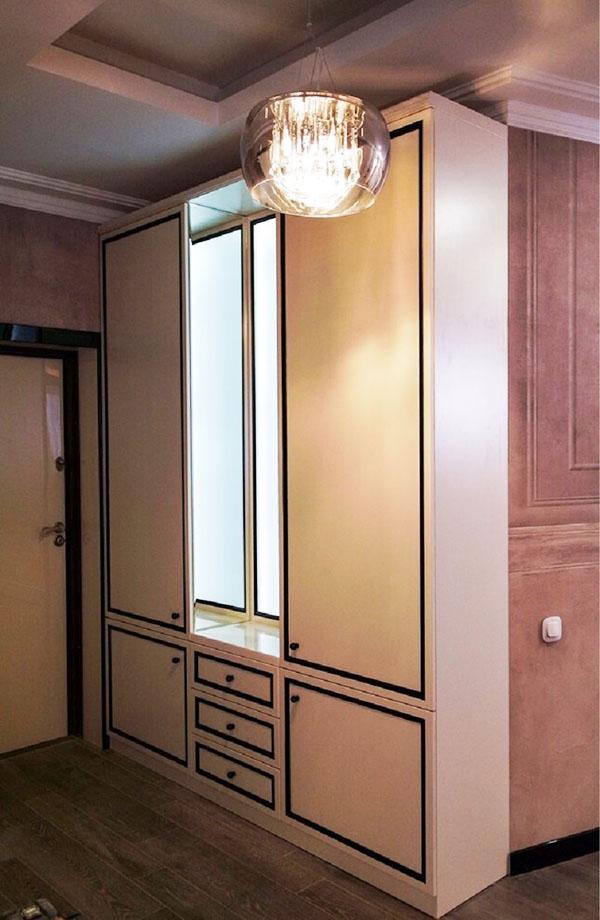 В прихожей установили высокий шкаф, зеркало которого по периметру украшено подсветкой