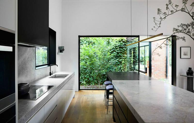 Панорамные окна и белые стены наполняют пространство светом, а единое покрытие пола добротной паркетной доской визуально связывает кухню и гостиную