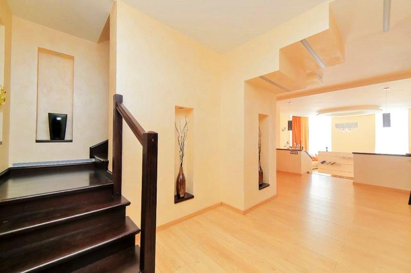 В холле на потолке установили многоступенчатую конструкцию из гипсокартона с линейной подсветкой каждого элемента
