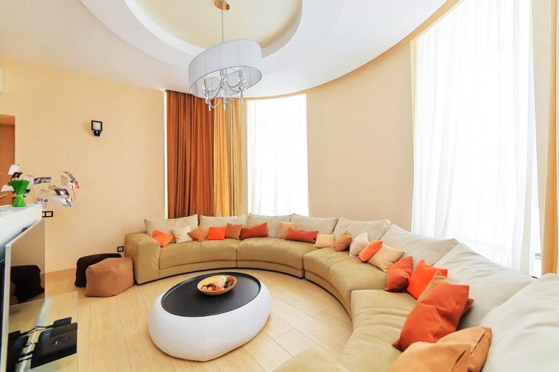 Для украшения окна в гостиной выбрали белоснежный тюль и однотонные портьеры песочного и коричневого оттенков