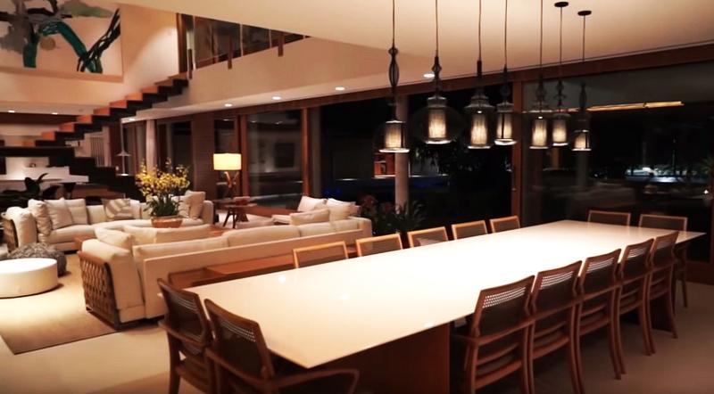 Освещает пространство ряд точечных светильников по периметру, огромная люстра и подвесные дизайнерские фонари в чёрных каркасах над обеденной зоной