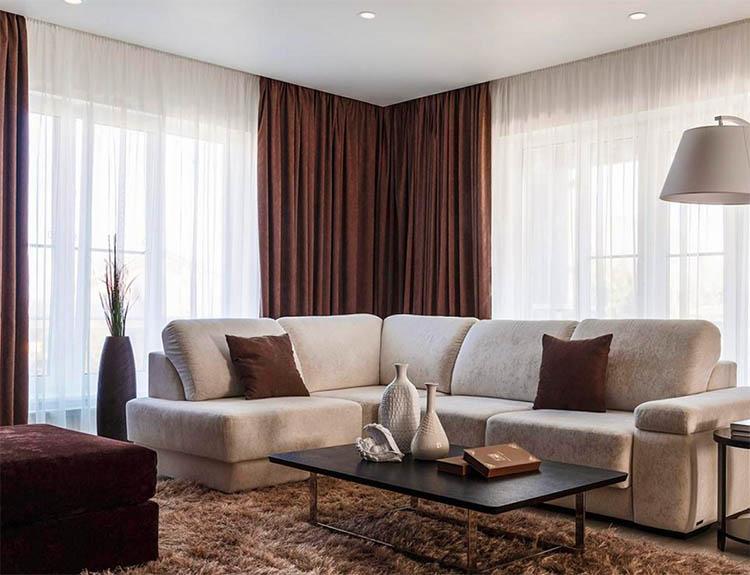 Панорамные окна украшает белоснежный тюль и однотонные портьеры шоколадного оттенка
