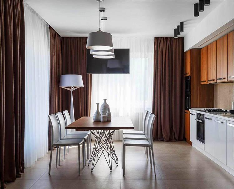Освещают кухню встроенная линейная подсветка над верхним модулем, точечные светильники и подвесные лампы над обеденной зоной