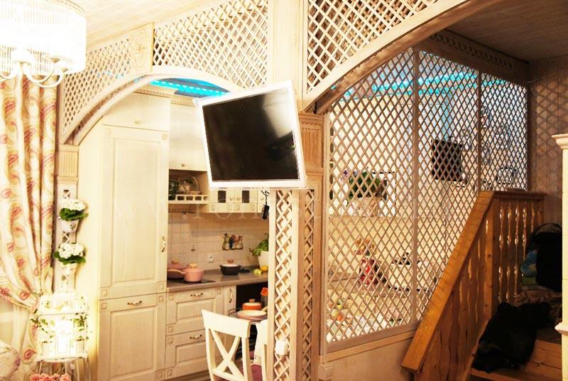 Небольшой телевизор идеально вписался в простенок между кухней и лестницей