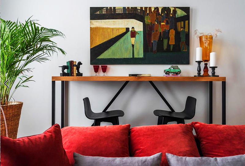 Гостиную украшают сразу несколько предметов: картина над столом, яркая жёлто-оранжевая ваза и большое растение в кадке
